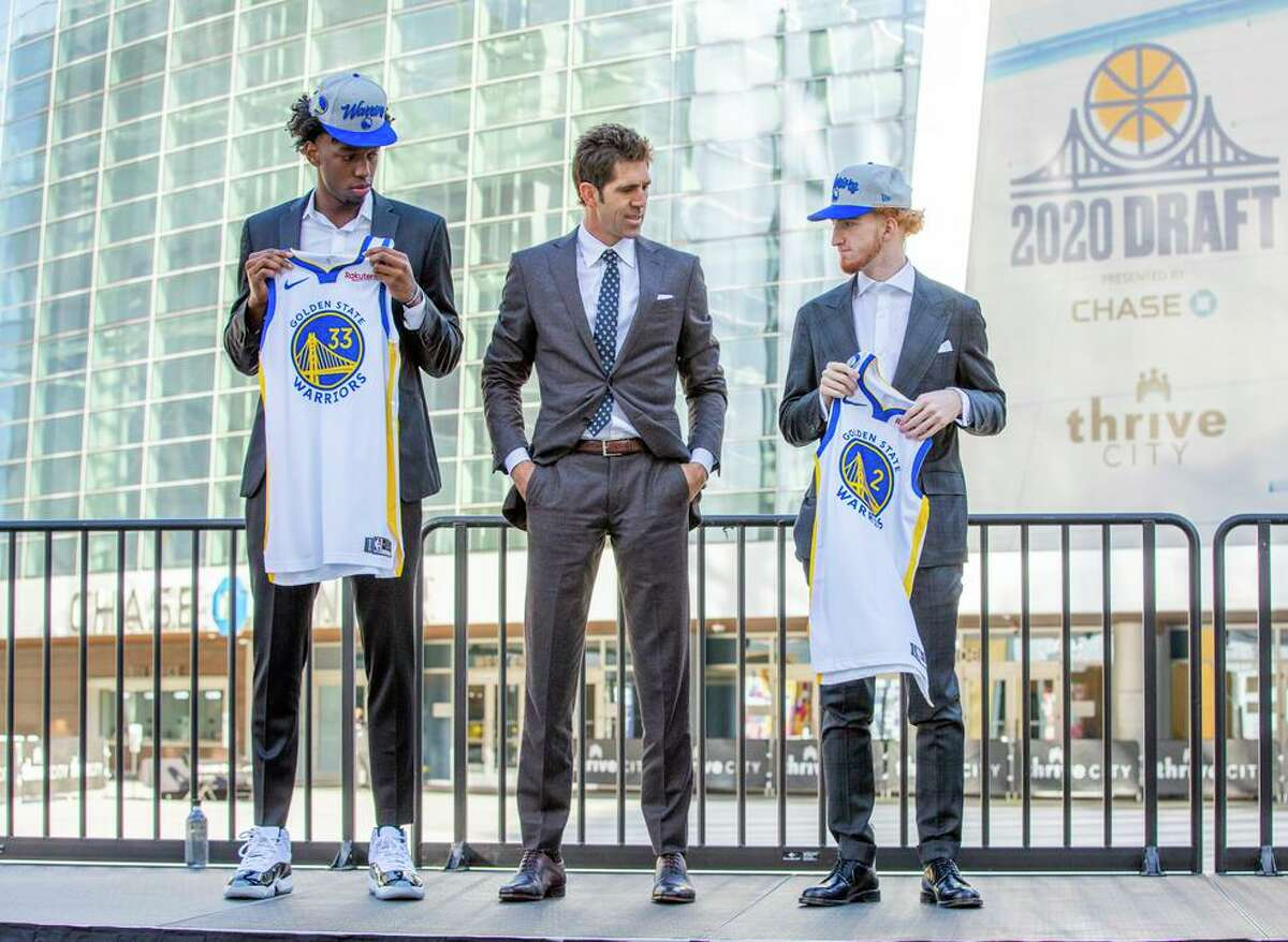 Warriors' center James Wiseman (left), general manager Bob Myers and guard Nico Mannion with their jerseys.