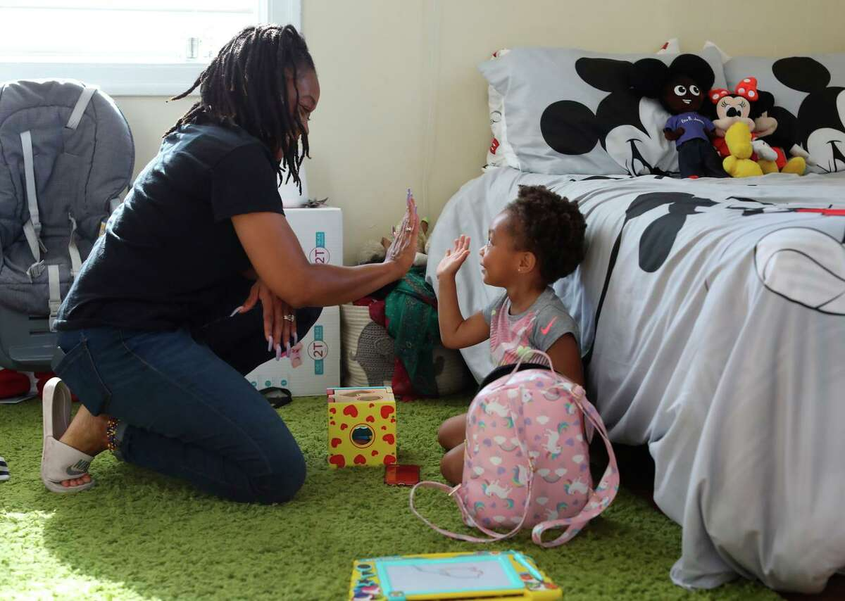 Sharayah Alexander high-fives daughter Savannah, 2, in their Vallejo home. Alexander is involved in the Deliver Birth Justice campaign to reduce Black maternal and infant mortality.
