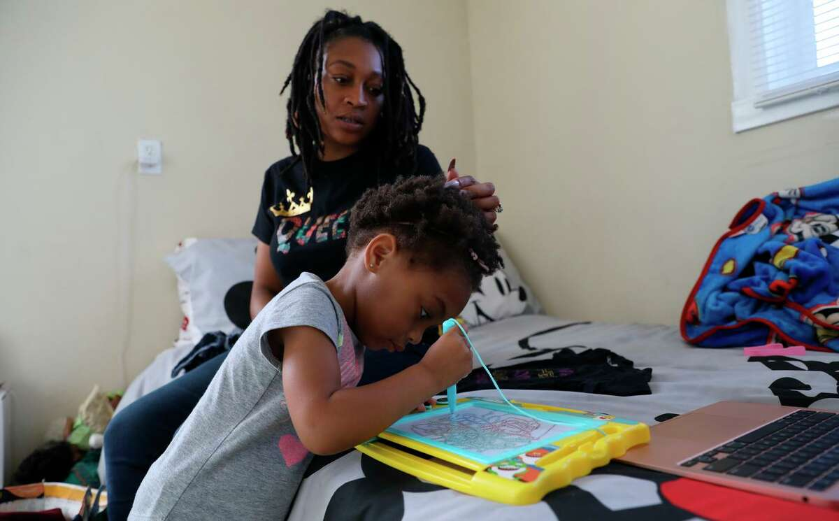 Sharayah Alexander, 32, shown with 2-year-old Savannah, attends a webinar on scholarships for entrepreneurs. Alexander is involved in the Deliver Birth Justice campaign to reduce Black maternal and infant mortality.