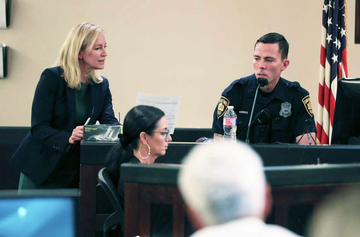 San Antonio Police officer Parker Morris (right) looks over a booking sheet with state Prosecutor Tamara Strauch (left) as witnesses testify on the eighth day of Otis McKane's trial.