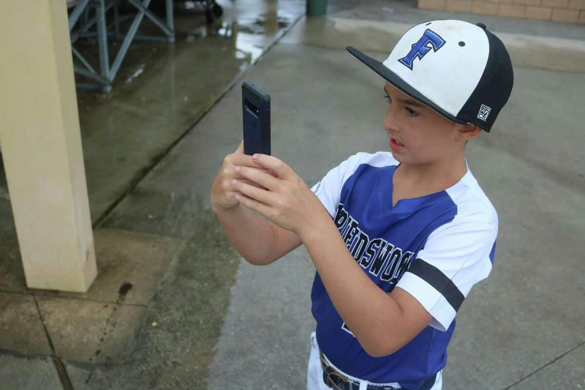 Friendswood's Aiden Flores takes a cell phone picture of other members of the team prior to their Pony South Zone game Wednesday afternoon.