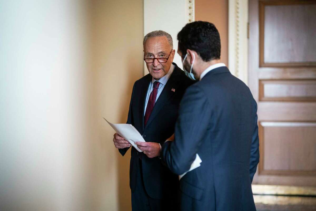 Senate Majority Leader Chuck Schumer, D-N.Y., reviews notes for a news conference earlier this week.