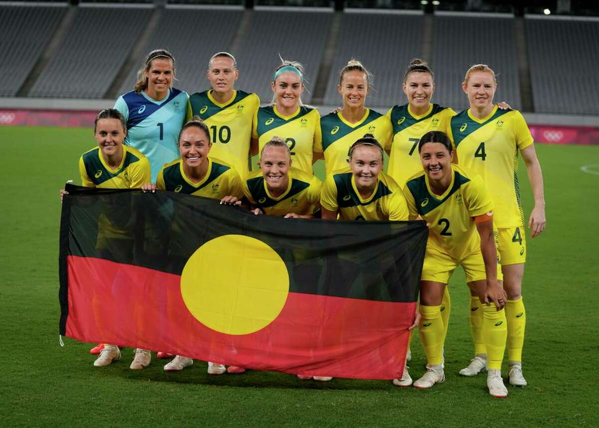 Australia players pose for a group photo with an Indigenous flag prior to their women's soccer match against New Zealand.
