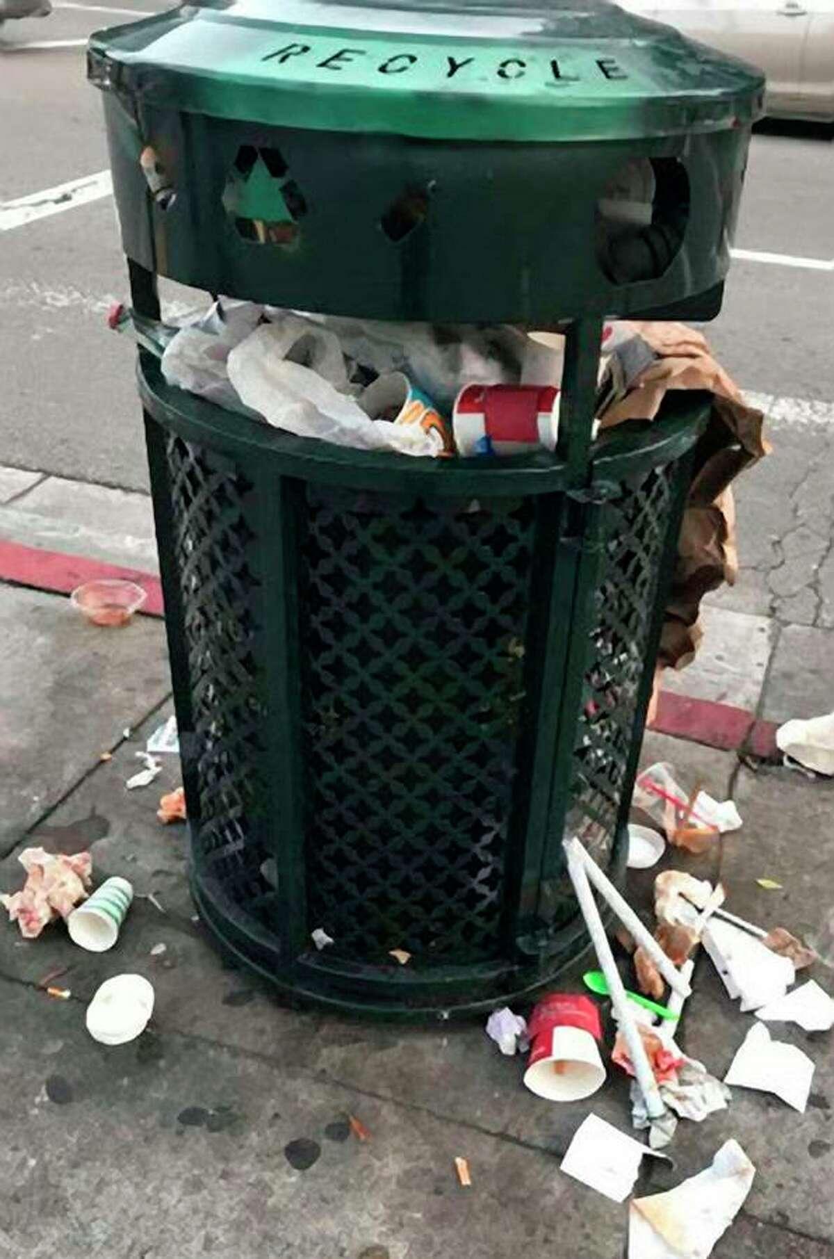 A trash overflows on a San Francisco sidewalk.