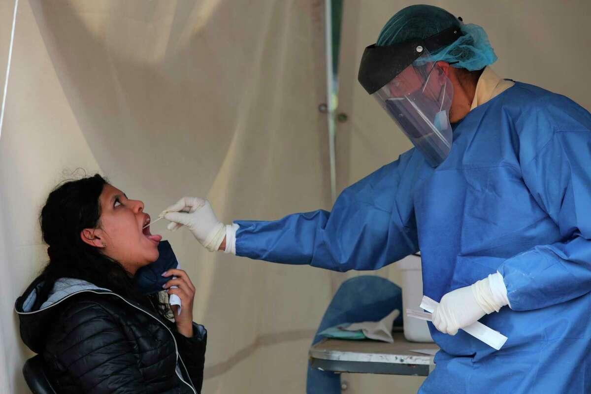 Un trabajador de la salud toma una muestra de la garganta de una mujer para hacer una prueba de detección de COVID-19 en Ciudad de México el sábado 10 de julio de 2021.
