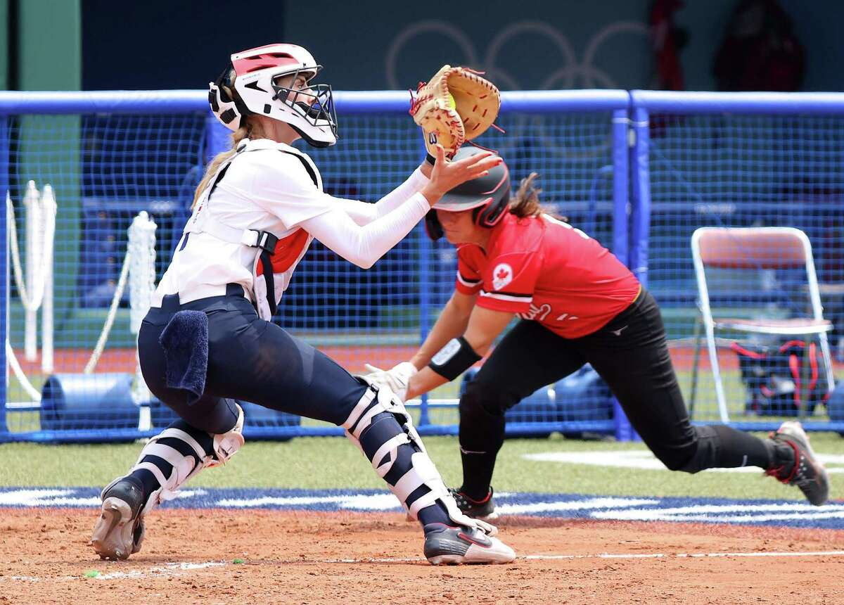 FUKUSHIMA, JAPAN - JULY 22: Catcher Aubree Munro #1 of Team United States catches the throw to the plate before tagging out Joanne Lye #5 of Team Canada trying to score in the sixth inning during the Softball Opening Round of the Tokyo 2020 Olympic Games at Fukushima Azuma Baseball Stadium on July 22, 2021 in Fukushima, Japan. (Photo by Yuichi Masuda/Getty Images)