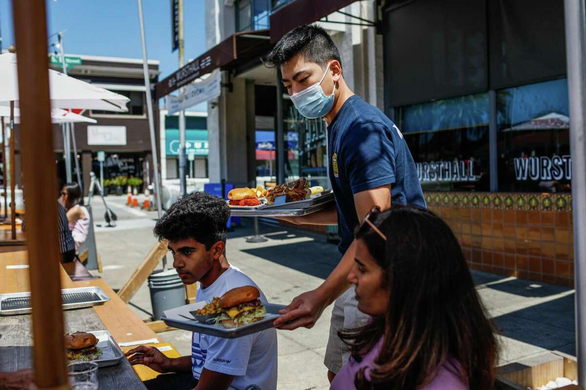 Server Brett Kuwahara (center) wears a mask as he carries plates to diners at Wursthall in San Mateo.