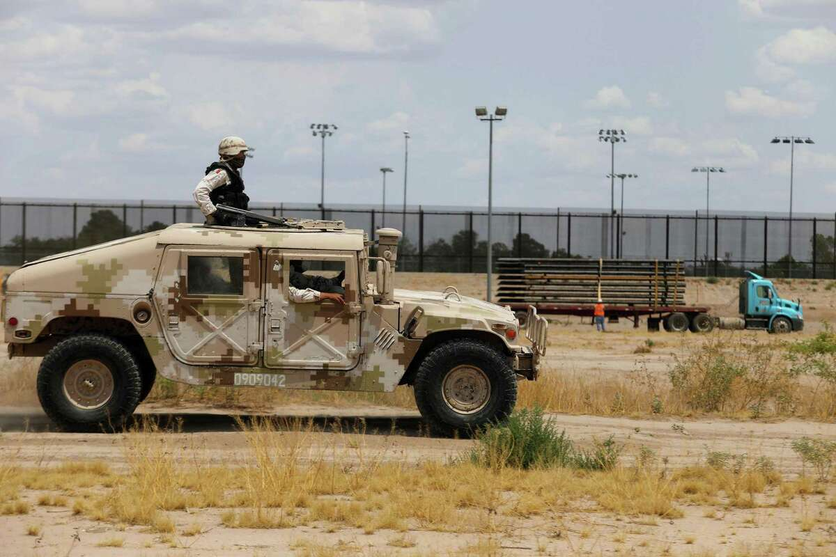 Members of the Mexican National Guard patrol along the Rio Grande, near the construction site of a new section of the border wall between El Paso, Texas, and Ciudad Juarez, Mexico, on Aug. 17, 2020. (Herika Martinez/AFP via Getty Images/TNS)