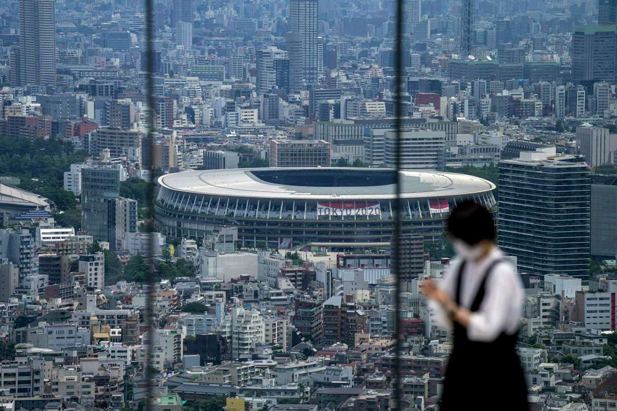 FILE - In this July 10, 2021, file photo, a person takes a picture from an observation deck as National Stadium, where the opening ceremony of the Tokyo 2020 Olympics will be held in less than two weeks is seen in the background in Tokyo.