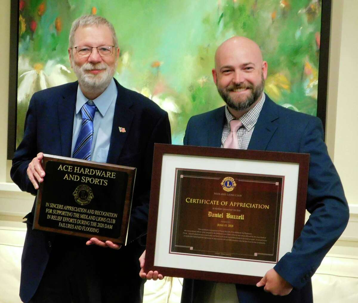 Ace Hardware and Sports owner Greg White, left, and manager Daniel Buzzell recently received awards from the Midland Lions Club for their help with the club's project of providing cleaning materials to flood victims.