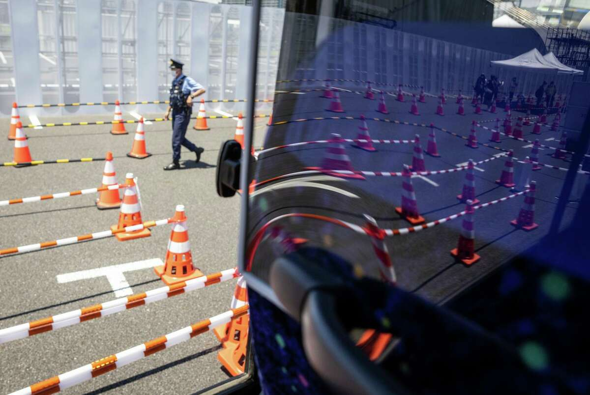 Rows of cones forming lanes for the media are distorted in the view from a plastic COVID screen at the main transport hub, ahead of the Tokyo 2020 Olympic Games on July 22, 2021 in Tokyo, Japan.