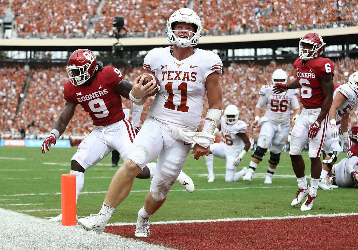UT quarterback Sam Ehlingersmiles as he runs into the endzone for a touchdown against the Oklahoma Sooners in the second quarter of the 2018 AT&T Red River Showdown at Cotton Bowl on October 6, 2018 in Dallas, Texas.
