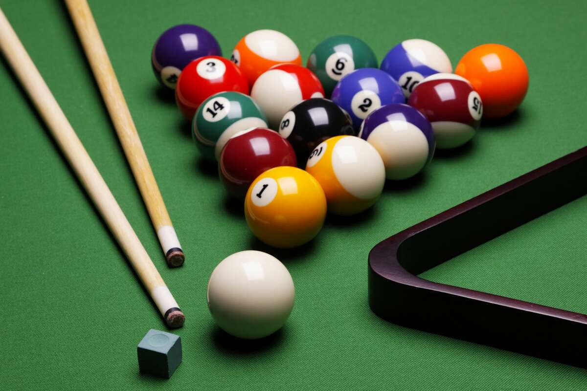 The photo shows the composition of billiard balls on a table with a triangle, balls and sticks and elements to the game of billiards.
