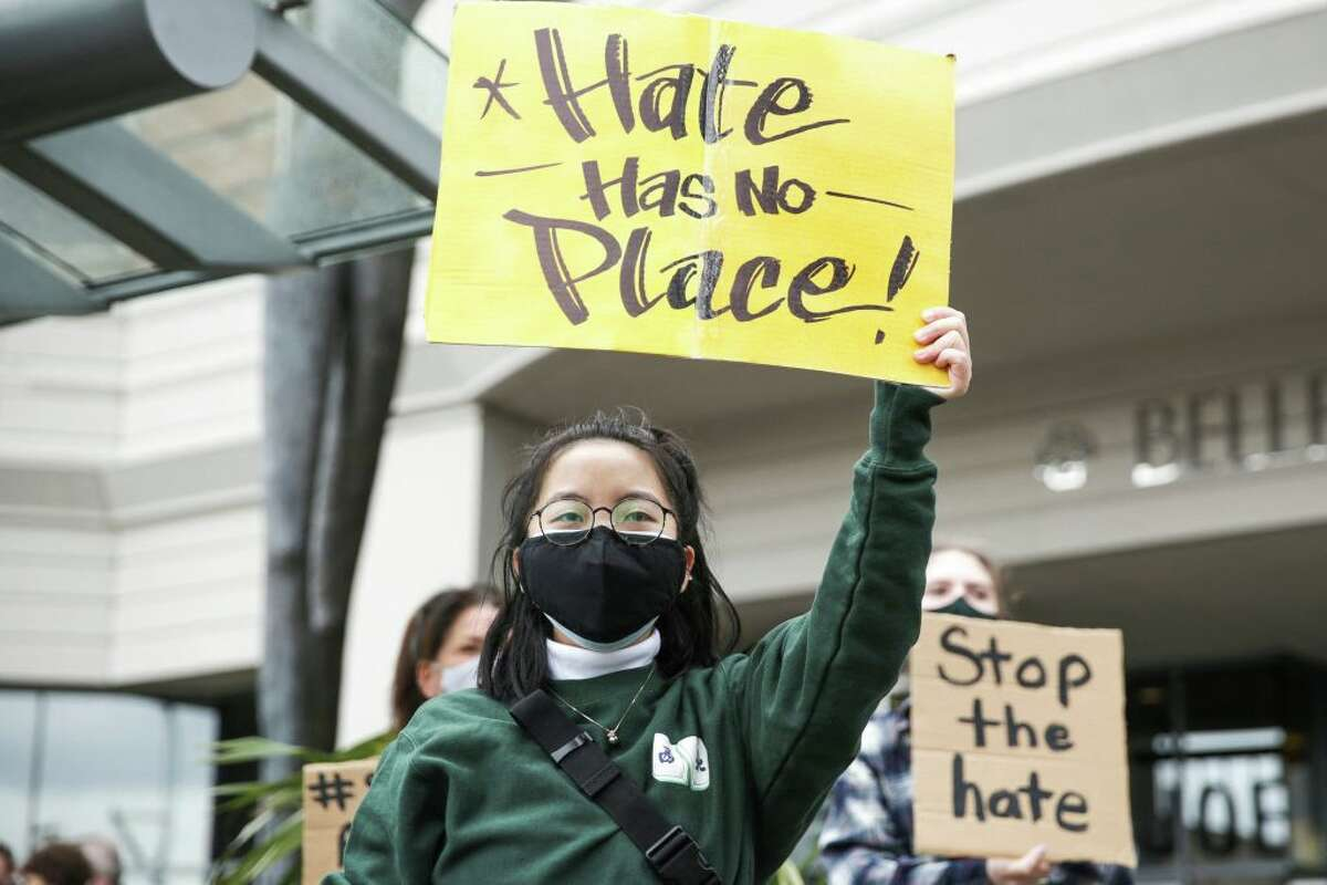 A protestor holds a sign advocating for the end of hate crimes.