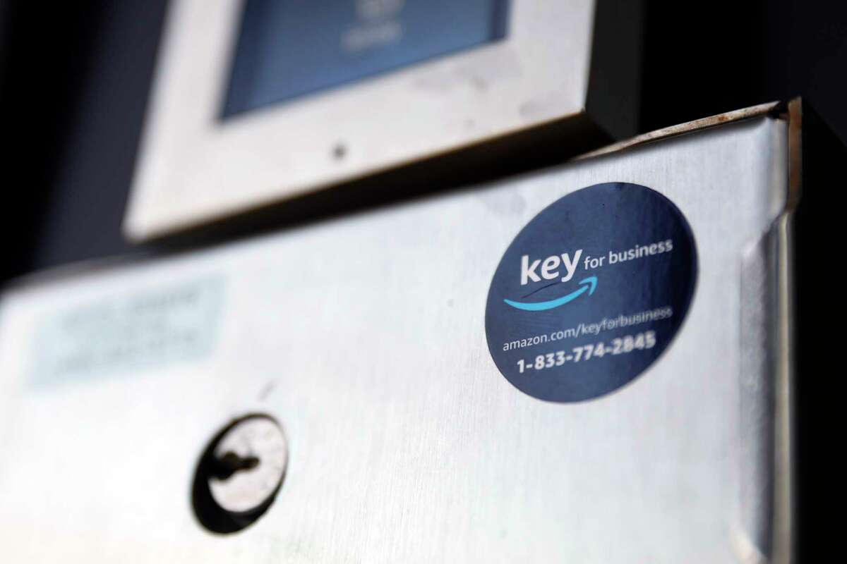 A blue sticker with the Amazon logo is displayed on a buzzer system in the apartment building of Jason Goldberg, chief commerce strategy officer at marketing company Publicis Communications, Monday, March 29, 2021, in Chicago. Amazon is making a push to install a device on buzzer systems in apartment buildings throughout the country that allows its delivery drivers to whip out a phone, tap a button and unlock a building's front doors whenever they need to leave packages in the lobby instead of the street.