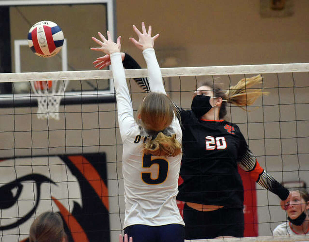 Edwardsville senior middle blocker Storm Suhre tips an attack past an O'Fallon blocker during a Southwestern Conference match.