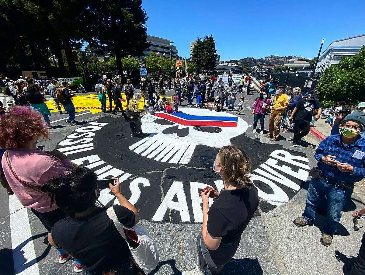 Community members gather around a street painting completed by attendants of the 8th annual Anti-Chevron Day at the Chevron oil refinery in Richmond, California on May 21, 2021.