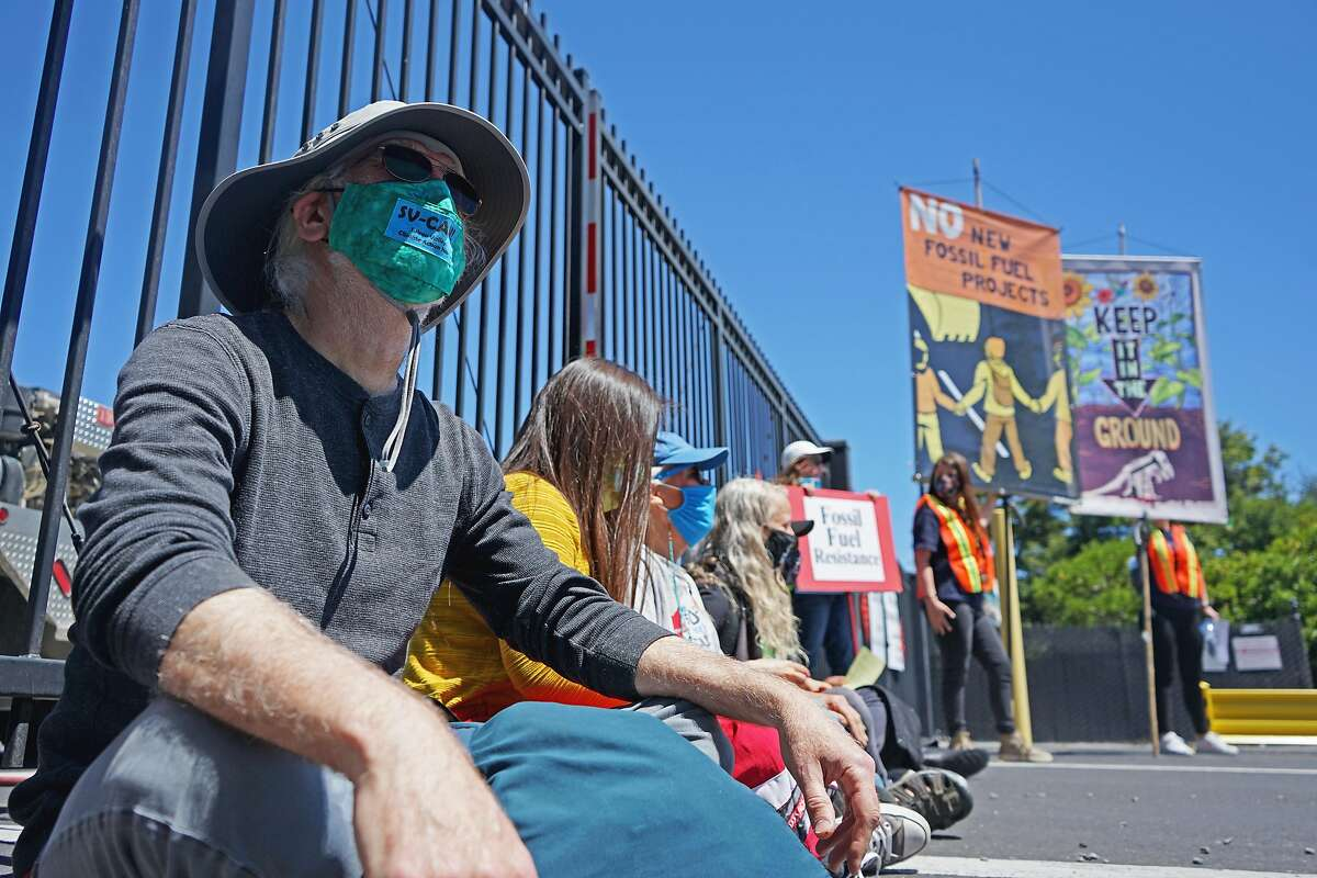 A group of activists sit in front of the Castro Street gate entrance of the Chevron oil refinery in Richmond to block Chevron Fire Station vehicles from wetting the pavement where protesters started painting an art piece during the 8th annual Anti-Chevron Day at the Chevron refinery in Richmond, California on May 21, 2021.