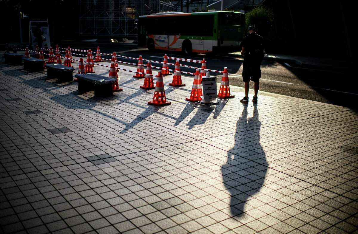 TOKYO, JAPAN - JULY 22: A journalist stands near a bus stop for media transport ahead of the Tokyo 2020 Olympic Games on July 22, 2021 in Tokyo, Japan. (Photo by Matthias Hangst/Getty Images)