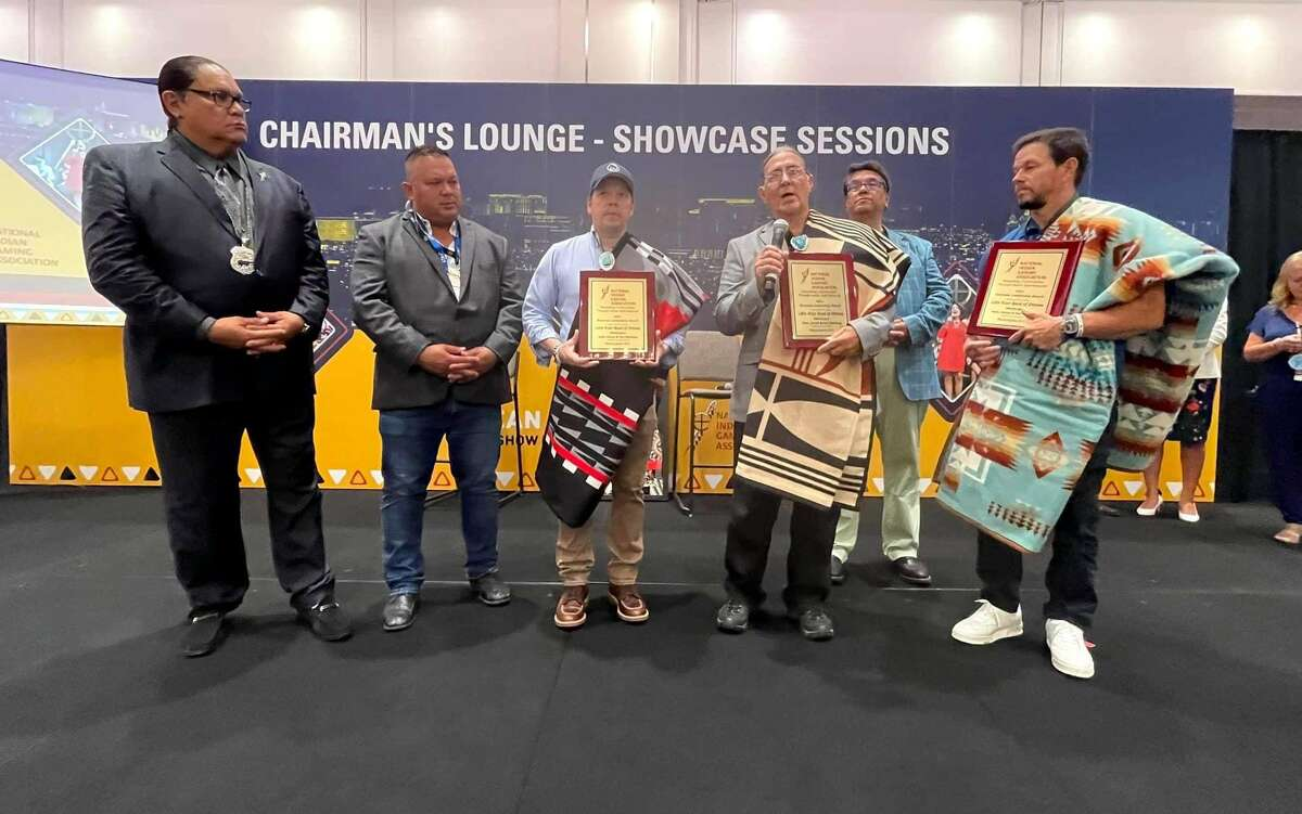 National Indian Gaming Association chairman Ernie Stevens (left) presents the Business Leadership Award to Little River Band of Ottawa Indian members Eugene Magnuson (back) and Paul and Mark Wahlberg.