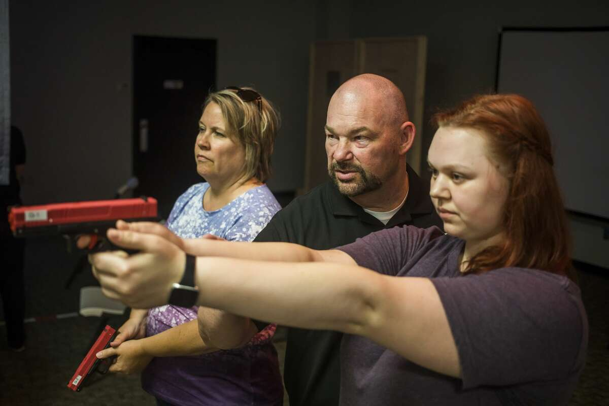 Instructor Craig Moyers, center, teaches the proper grip to Pam Doran of Merrill, left, and Heather Royce of Midland, right, during the first Women's Shooter Wednesday event hosted by Applied Training Solutions Wednesday, July 21, 2021 at the Midland Mall. (Katy Kildee/kkildee@mdn.net)