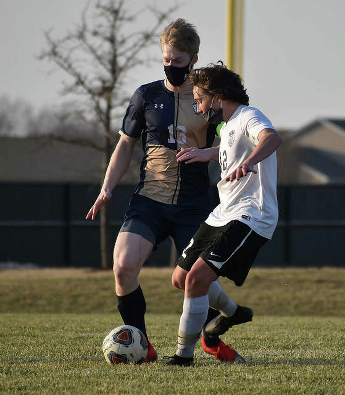 Father McGivney midfielder Matthew Gierer battles for a 50-50 ball at midfield during the first half of the Griffins' season opener against Triad on March 9.