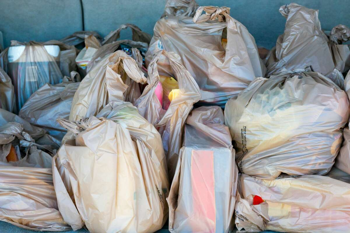 Plastic bags full of groceries in the trunk of a car.