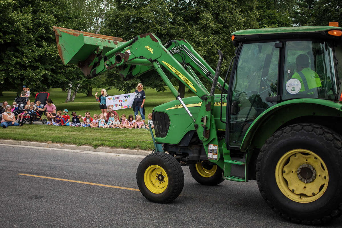 Families line up along Plymouth Park Drive to watch a contactless city vehicle parade featuring police cars, fire engines, garbage trucks and more Thursday, July 22, 2021 at Plymouth Park in Midland. (Katy Kildee/kkildee@mdn.net)