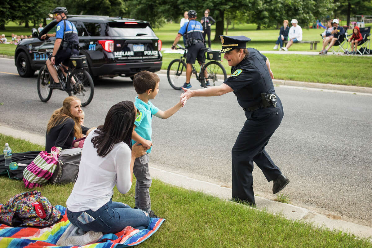 Midland Police Chief Nicole Ford greets families during a contactless city vehicle parade featuring police cars, fire engines, garbage trucks and more Thursday, July 22, 2021 at Plymouth Park in Midland. (Katy Kildee/kkildee@mdn.net)