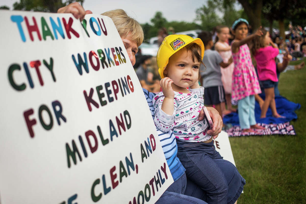 Mira Wenzloff, 18 months, watches during a contactless city vehicle parade featuring police cars, fire engines, garbage trucks and more Thursday, July 22, 2021 at Plymouth Park in Midland. (Katy Kildee/kkildee@mdn.net)