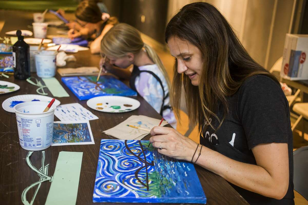 """Leanne Van Beek, right, and her daughter Claire, 9, center, work on their paintings during a """"Starry Tridge"""" painting class lead by Creative 360 Executive Director Laura Vosejpka Wednesday, July 21, 2021 at the Midland Mall. (Katy Kildee/kkildee@mdn.net)"""