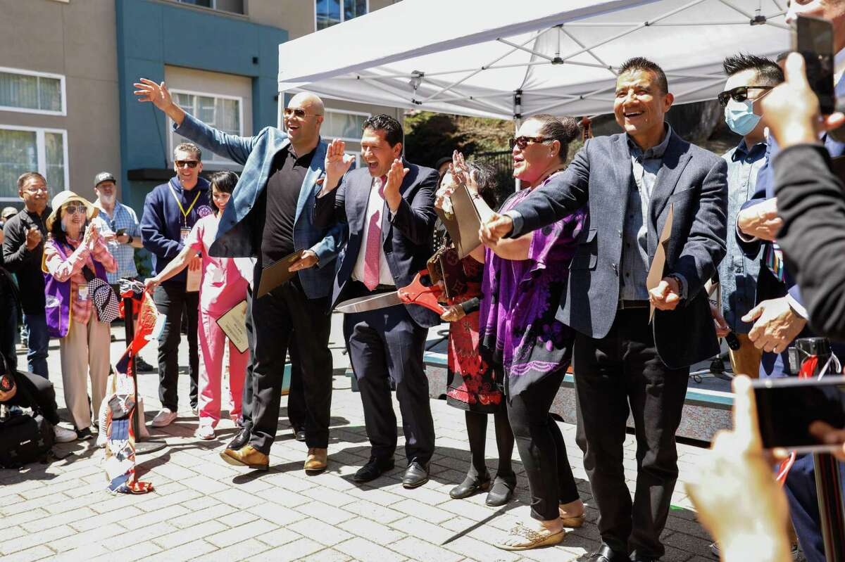 David J. Canepa (center), president of the San Mateo County Board of Supervisors, cheers alongside others at a California reopening celebration in Colma in June. Now, however, mask recommendations and requirements are spreading for even vaccinated people, as the delta variant takes hold.