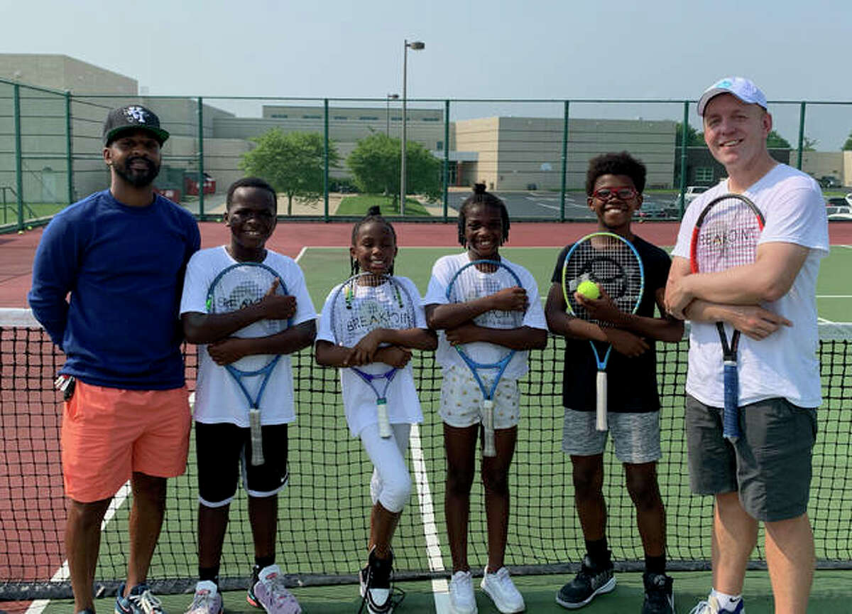 Members of Net Runners pose with Kweisi Kenyatte on one of the tennis courts at Liberty Middle School.