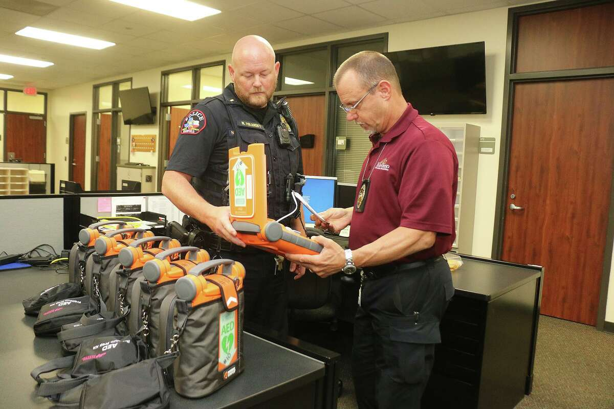 Klein ISD Police Chief David Kimberly and Lt. Nathan Polansky look over the newly delivered automated external defibrillators thanks to a grant from the Tomball Regional Health Services Foundation.