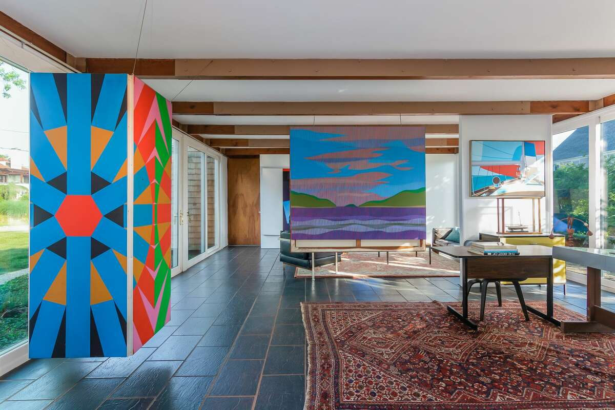 The family room inside the houseis lined with windows and offers multi-use living space that is currently used to display art. View listing