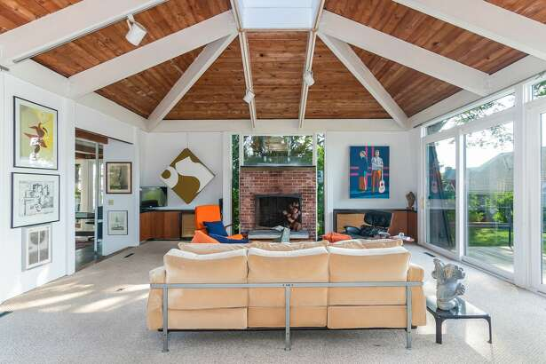 """The living room in the 105 Prospect Ave. home in Guilford, Conn., has high ceilings outfitted with a """"peaked skylight"""" and has doors leading out to an outdoor space."""