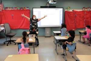 """Elyse Pastore teaches children a science class during summer school held for grades K-8 at Strawberry Hill School in Stamford, Conn., on Friday July 16, 2021. This summer, Stamford schools are offering six weeks of classes, for five hours a day, and an extra three hours every day for """"enrichment time"""" provided by a variety of community partners."""
