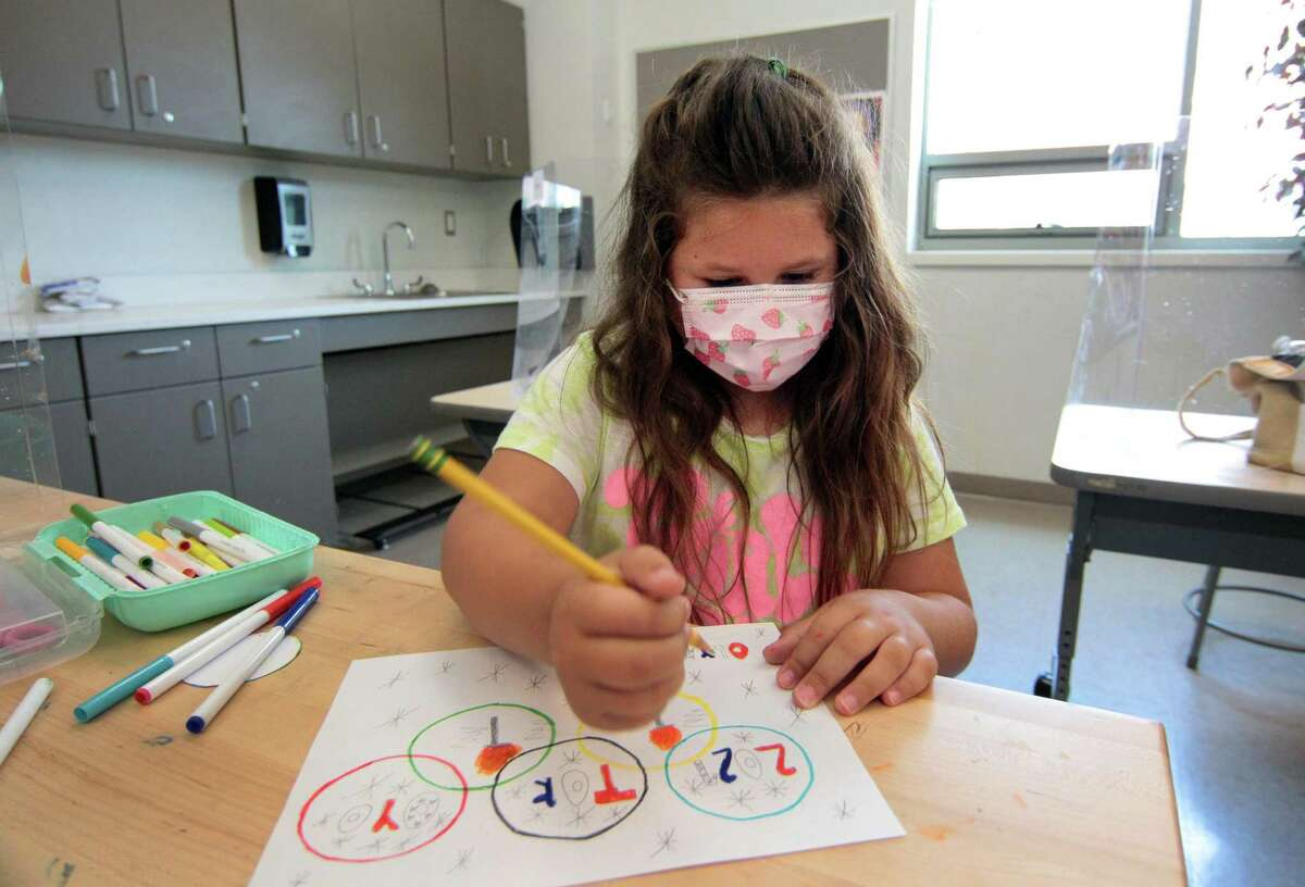Third grader Ava Calicchio draws the Olympic rings in an art class during summer school held for grades K-8 at Strawberry Hill School in Stamford, Conn., on Friday July 16, 2021.