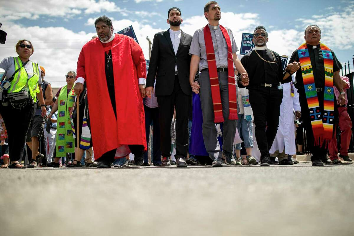 """Rev. Dr. William J. Barber II, left, Imam Omar Suleiman middle-left, and other clergy members from all faiths from around the country walk to the entrance of the DHS offices where migrants are housed during the """"Moral Monday at the Borderlands"""" demonstration, Monday, July 29, 2019, in El Paso, Texas. Photo by Ivan Pierre Aguirre"""