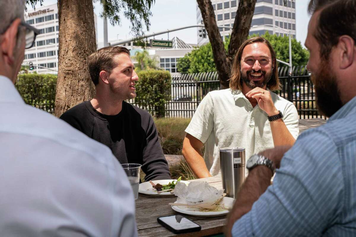 Tom Hammel, left, and Darren D'Altorio, right, enjoy the camaraderie of a return to the office June 29, 2021, in El Segundo, Calif. Los Angeles County has since reimposed indoor mask mandates.