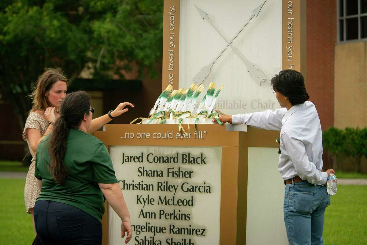 """Corrigan Garcia, who graduated from Santa Fe High School in 2018, and Maegan Huddleston, who graduated in 2019, and Megan Grove, who chair's the Santa Fe Ten Memorial Foundation, place 10 feathers representing the 10 victims of the 2018 Santa Fe High School shooting on the new memorial to the 10 victims, Tuesday, May 18, 2021, outside of the high school in Santa Fe. The Santa Fe Ten Memorial Foundation unveiled the """"Unfillable Chair,"""" a student-designed memorial, on the third anniversary of the shooting. The foundation is planning a larger memorial for the future."""