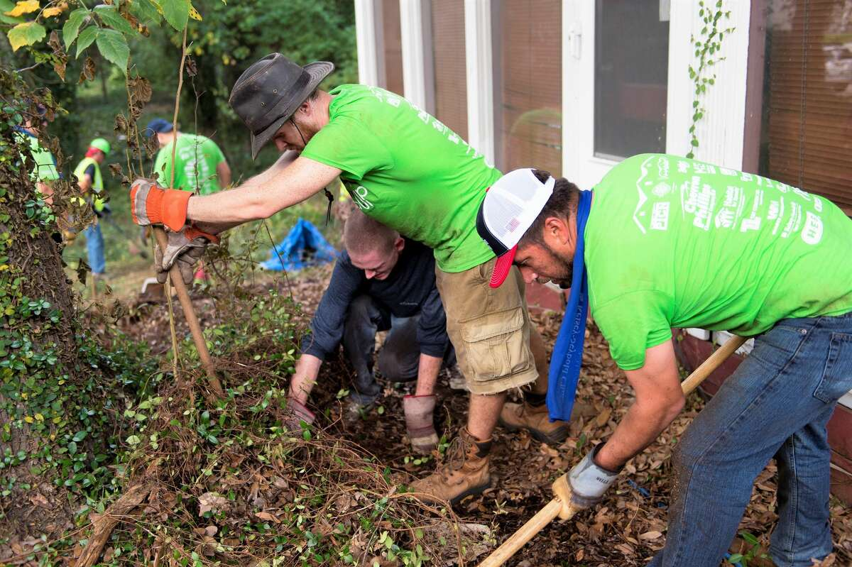 Volunteers get down and dirty doing yard work at a Team Up to Clean Up event.
