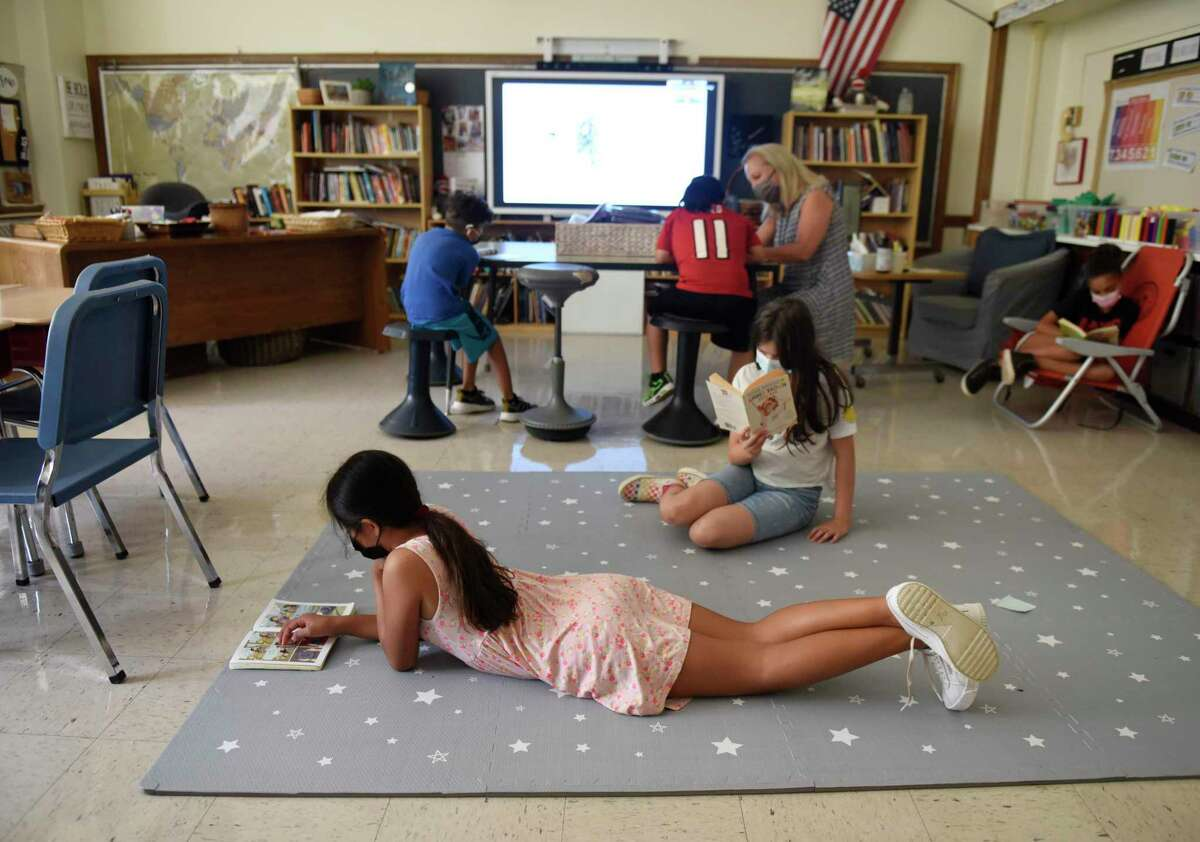 Rising fourth-graders Johana Diaz, left, and Amy Lou Restrepo read on the floor during the summer academy at Julian Curtiss School in Greenwich, Conn. Tuesday, July 20, 2021. About 50 kindergarten through fifth-graders are attending the summer enrichment camp, which runs every morning from 8:30 to 11:30 a.m.