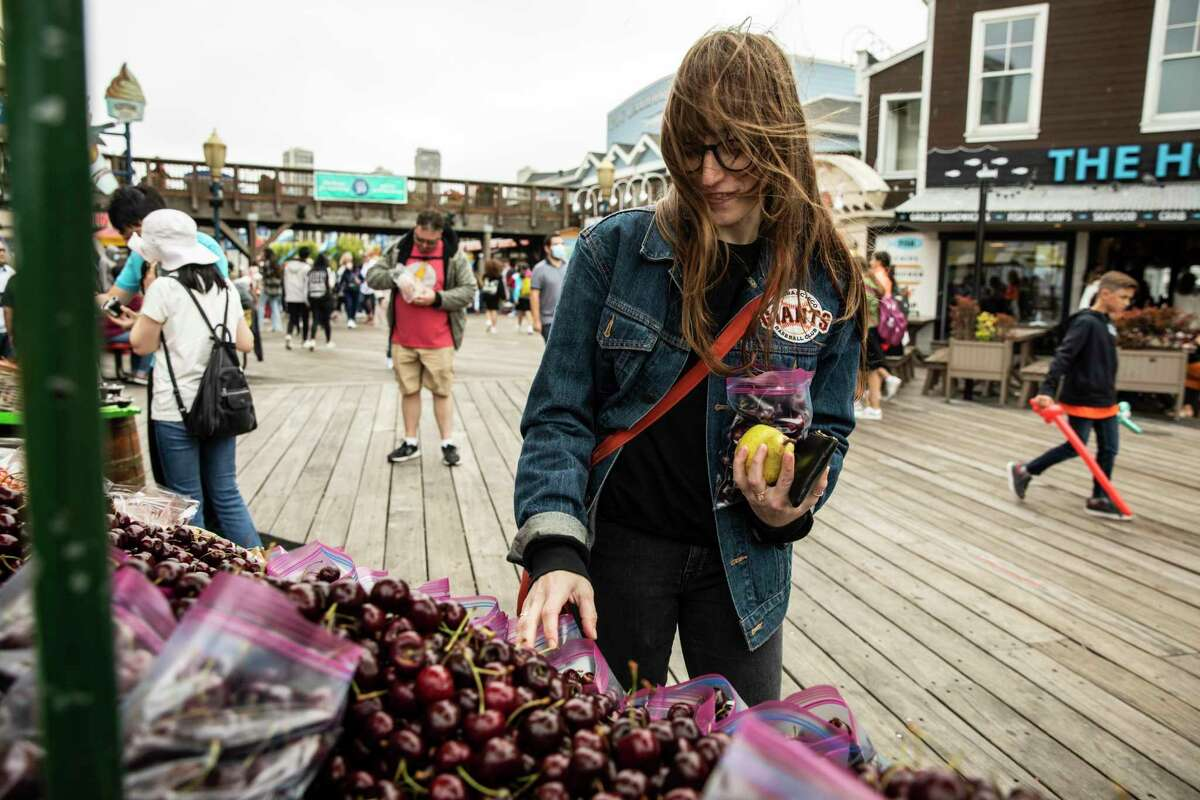 Becca Camping, a restaurant worker whose unemployment benefits were frozen after she was laid off last year due to the pandemic, shops for fruit at Fisherman's Wharf in San Francisco.