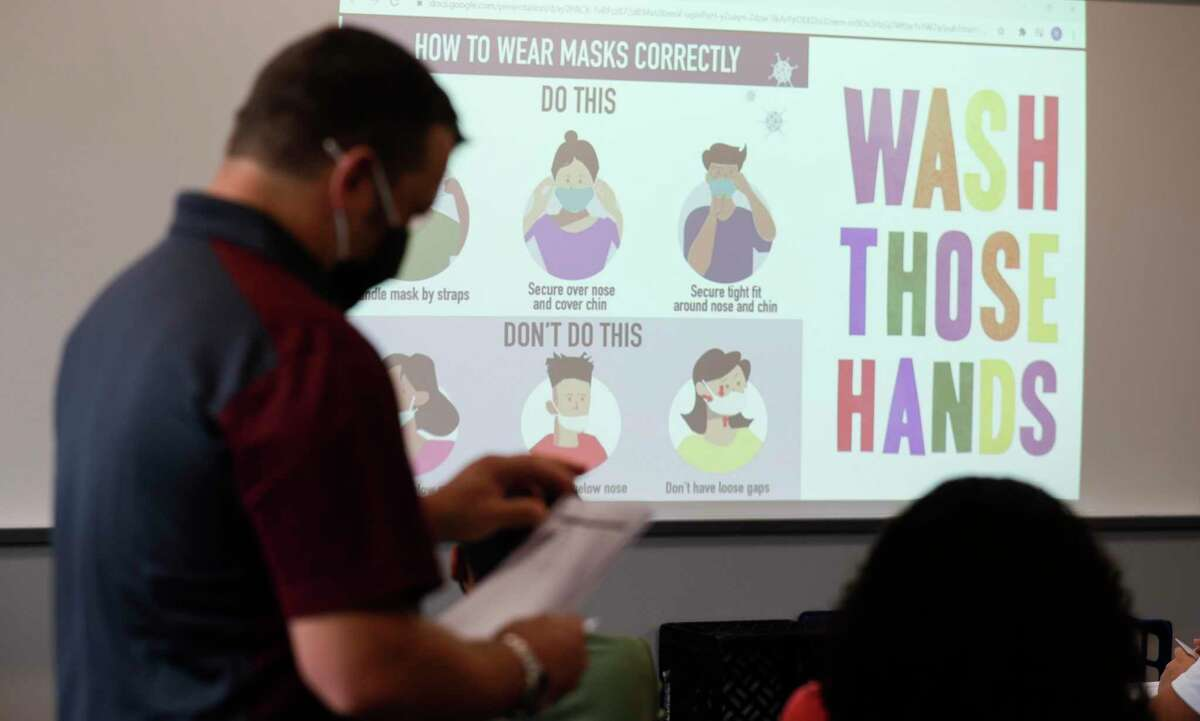 A slide in history teacher Robert Simard'a classroom reminds students how to properly wear their masks and reminds them to wash their hands at Stockton Junior High School on the first day of in-person school for Conroe ISD on Sept. 8 in Conroe. CISD administrative officials have released the preliminary assessment results from this year's STARR tests.