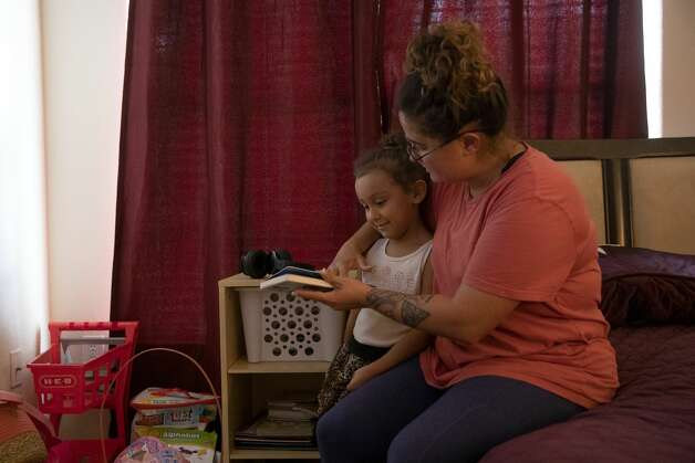 Brittany Aguirre reads to her daughter, Brielle. Since getting clean spending time with her daughter has been a priority. Most weekends Brittany spends with Brielle at her home working to reconnect after years apart. Photo: Jessica Phelps/San Antonio Express-News / **MANDATORY CREDIT FOR PHOTOG AND SAN ANTONIO EXPRESS-NEWS/NO SALES/MAGS OUT/TV  © 2021 San Antonio Express-News