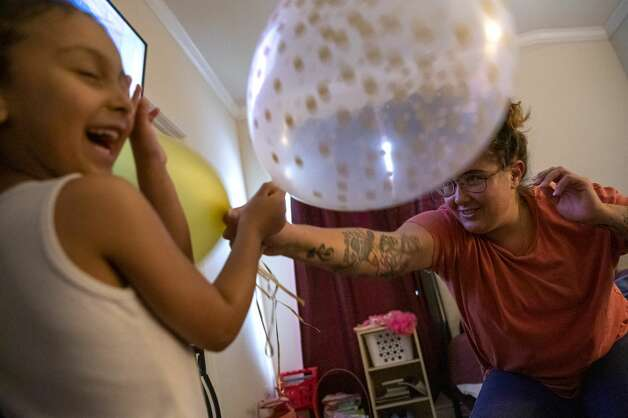 Brittany Aguirre takes the lead in a balloon fight against her daughter, Brielle. Since getting sober spending time with her daughter has become a priority. Photo: Jessica Phelps/San Antonio Express-News / **MANDATORY CREDIT FOR PHOTOG AND SAN ANTONIO EXPRESS-NEWS/NO SALES/MAGS OUT/TV  © 2021 San Antonio Express-News