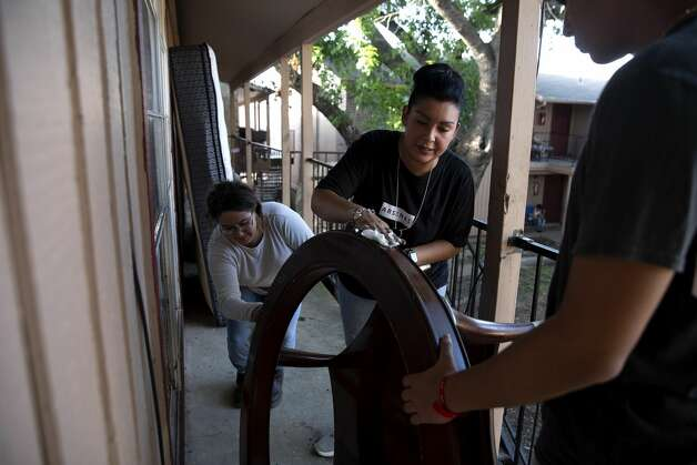 Brittany Aguirre, Valerie Salas and her son Xavier clean a table before moving in into her new home. Valerie, who is an outreach worker helped rally her neighbors to get furniture donated for Brittany who was moving into her first apartment after getting sober. Photo: Jessica Phelps/San Antonio Express-News / **MANDATORY CREDIT FOR PHOTOG AND SAN ANTONIO EXPRESS-NEWS/NO SALES/MAGS OUT/TV  © 2021 San Antonio Express-News