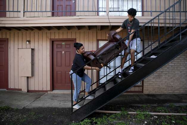 Valerie Salas and her son Xavier carry part of an armchair up a set of stairs for Brittany Aguirre. Valerie, who is an outreach worker helped rally her neighbors to get furniture donated for Brittany who was moving into her first apartment after getting sober. Photo: Jessica Phelps/San Antonio Express-News / **MANDATORY CREDIT FOR PHOTOG AND SAN ANTONIO EXPRESS-NEWS/NO SALES/MAGS OUT/TV  © 2021 San Antonio Express-News