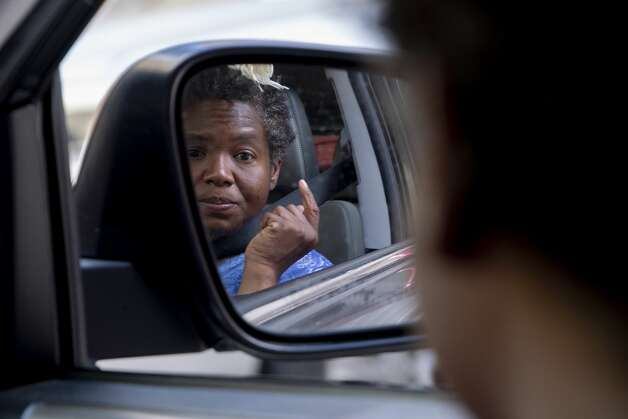 """""""Princess"""" checks out her reflection in the side mirror of outreach worker, Morgan Handley's car as she is driven to a medical clinic at Travis Park Methodist Church. Morgan picked Princess up downtown because she knew she had hurt her ankle a few day prior. Morgan was doubtful Princess would go with her because she is usually resistant to medical care. Photo: Jessica Phelps/San Antonio Express-News / **MANDATORY CREDIT FOR PHOTOG AND SAN ANTONIO EXPRESS-NEWS/NO SALES/MAGS OUT/TV  © 2021 San Antonio Express-News"""